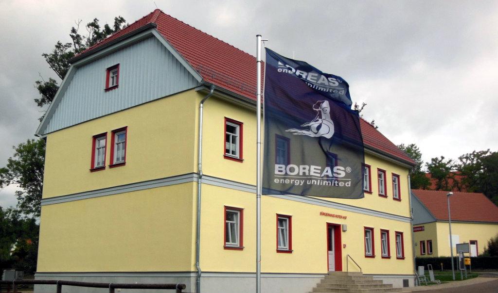A flag of the local wind developer in Gotha, Thüringen, waves outside a refurbished communal building