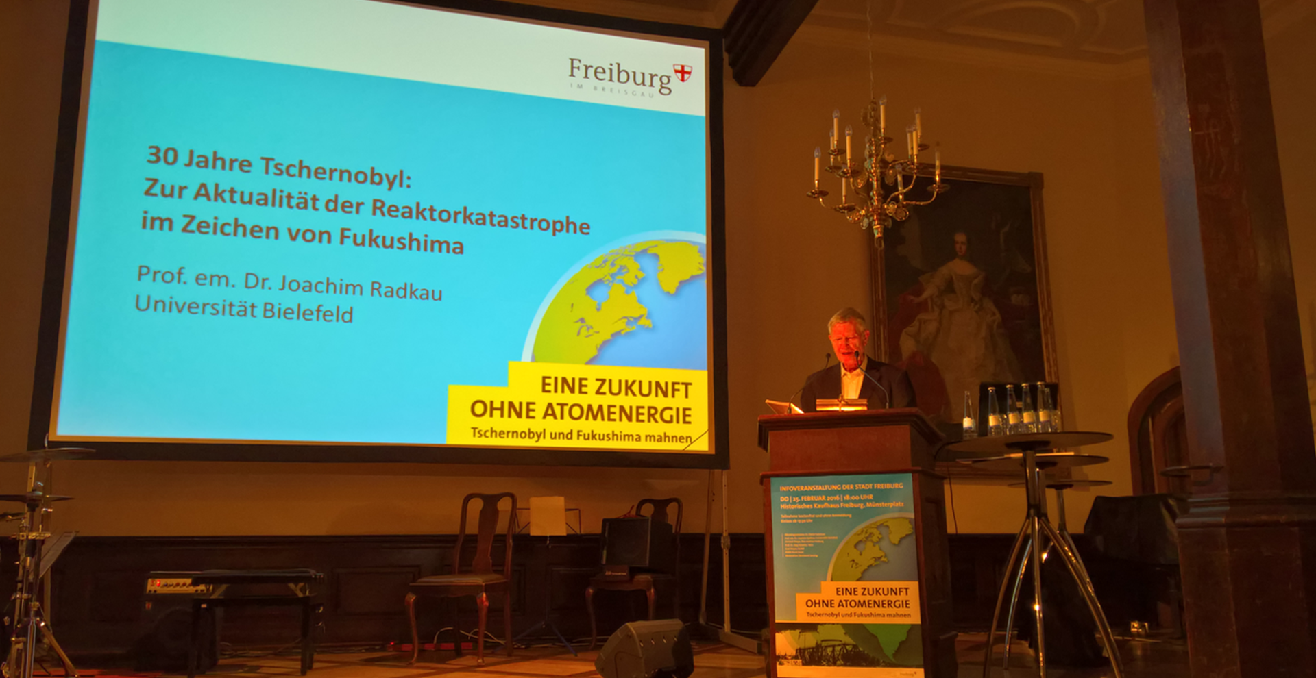 German energy sector historian Joachim Radkau is giving a speech next to a big screen with a presentation.