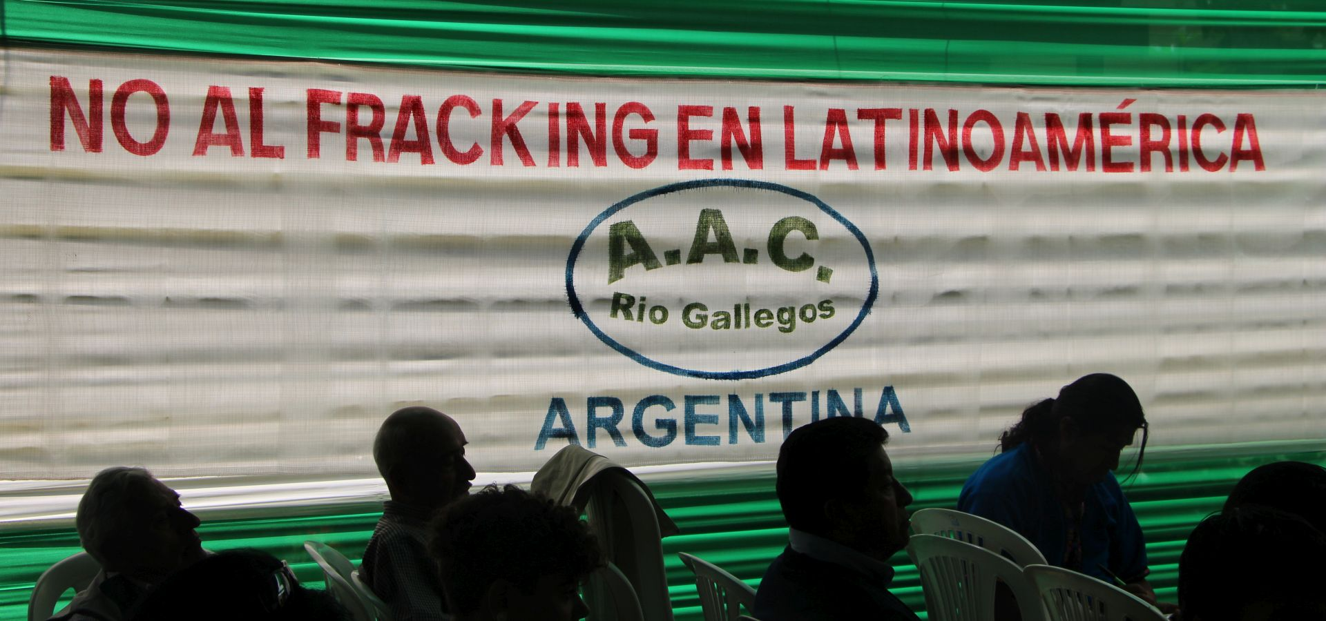 Silhouttes of people sitting in rows in the foreground, in the background a banner with a statement against fracking.