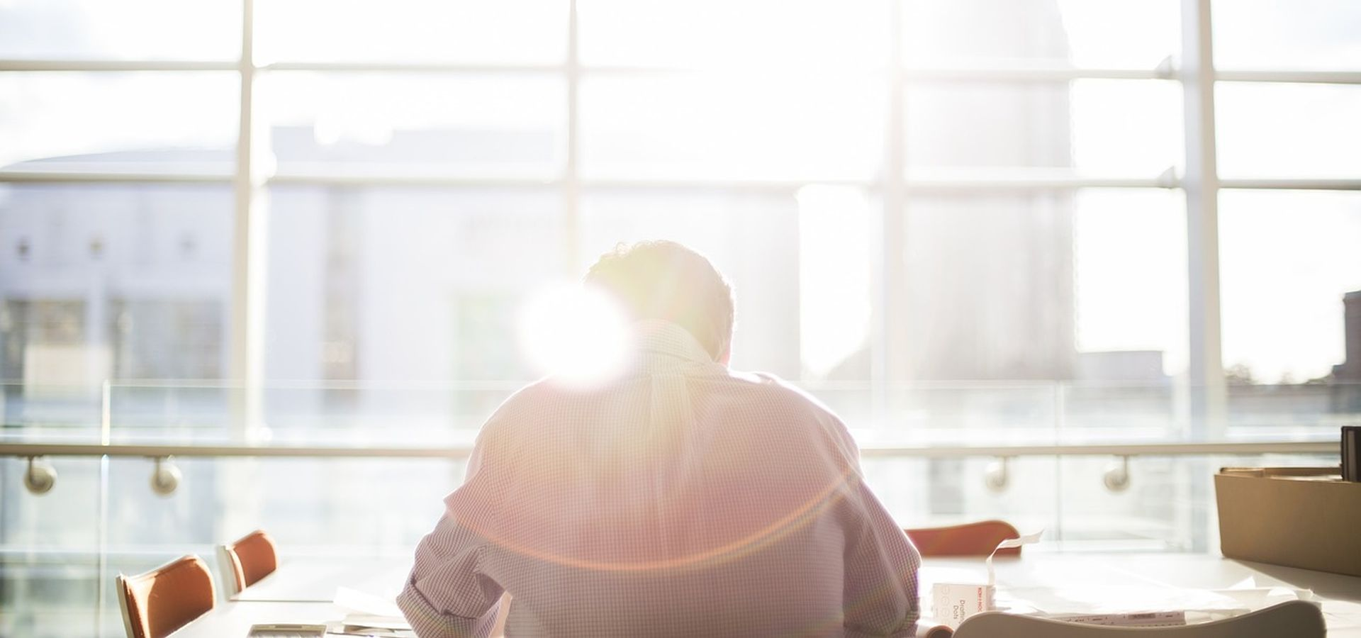 A man is sitting at a desk in front of a huge window where the sun is shining through.