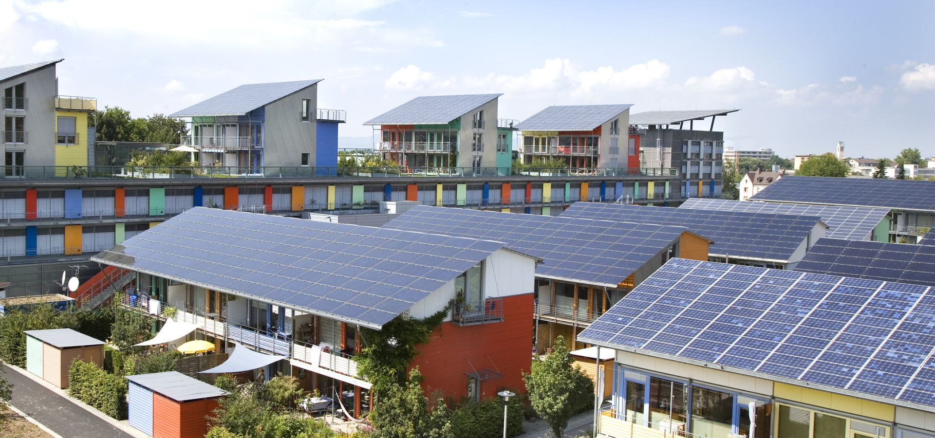 A lot of modern looking houses with solar cells on their roofs.