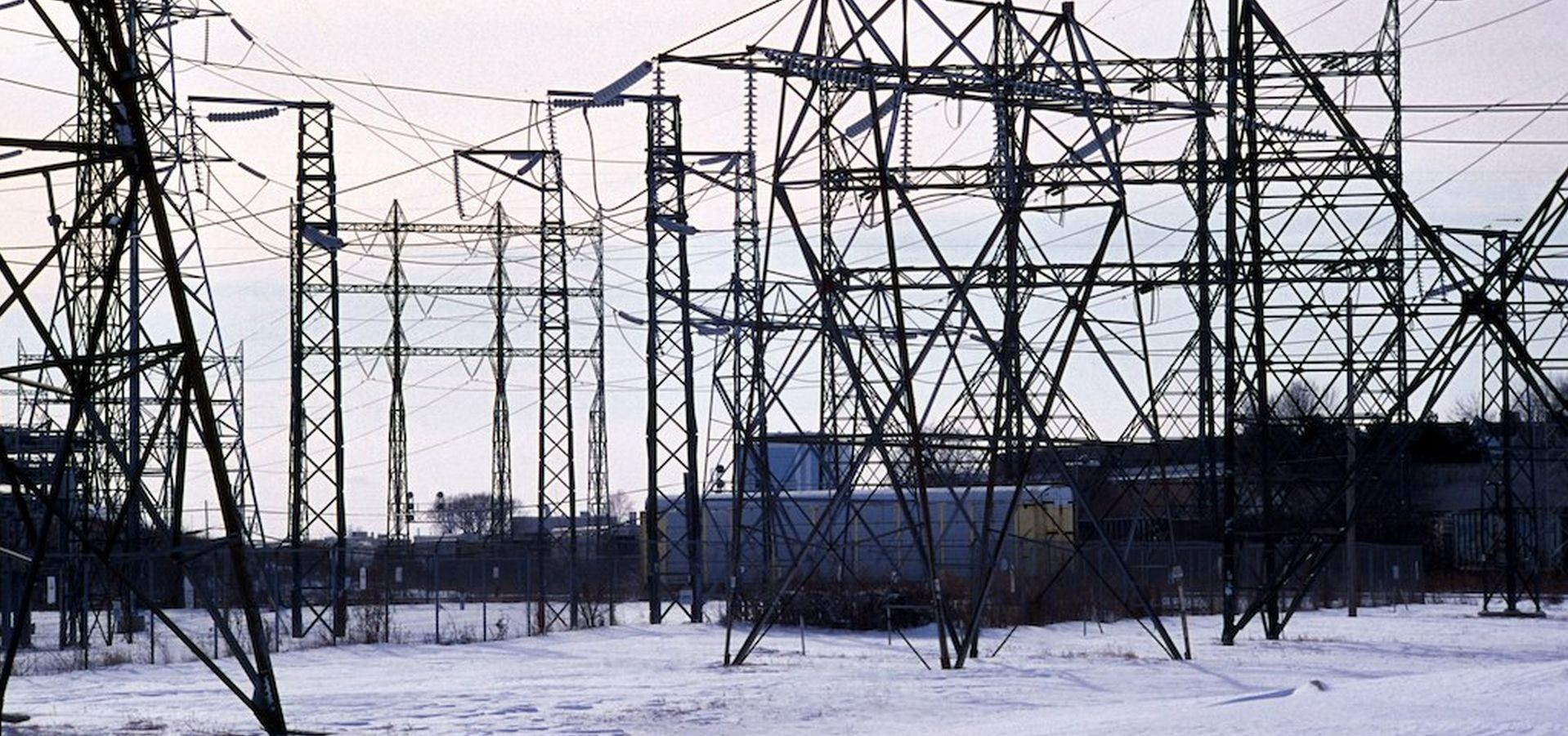 A landscape of power lines is covered with snow.
