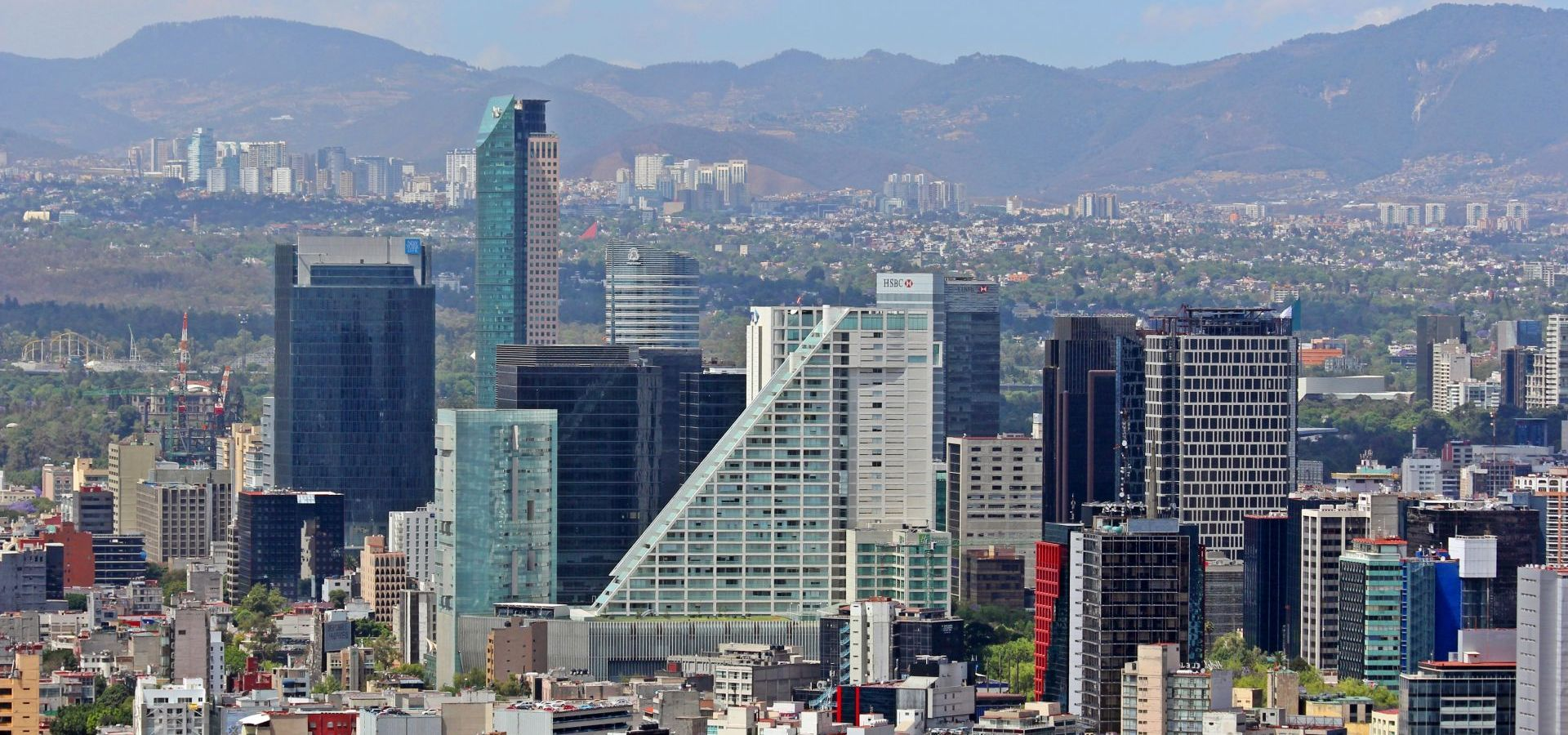 Skyscratchers of Mexico City with mountains in the background.