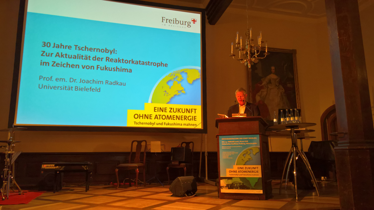 German energy sector historian Joachim Radkau is giving a speech in front of a screen with a presentation.