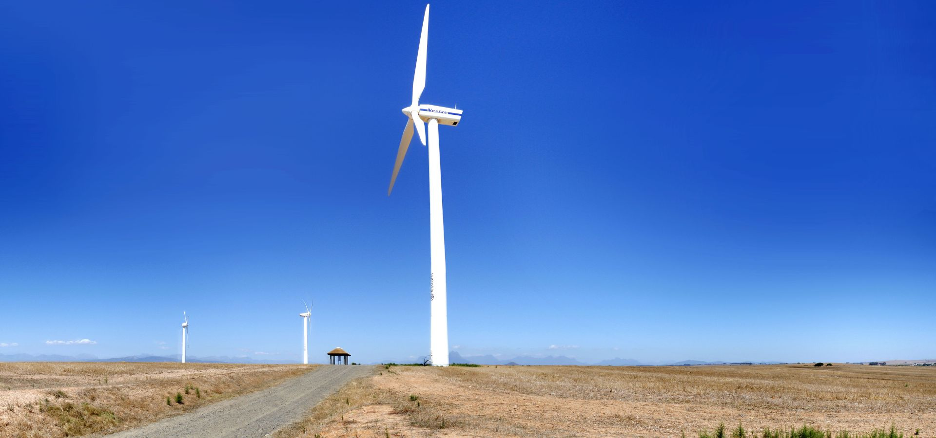 A wind mill in a very dry-looking are, the sun is shining and ther is no cloud in the sky.