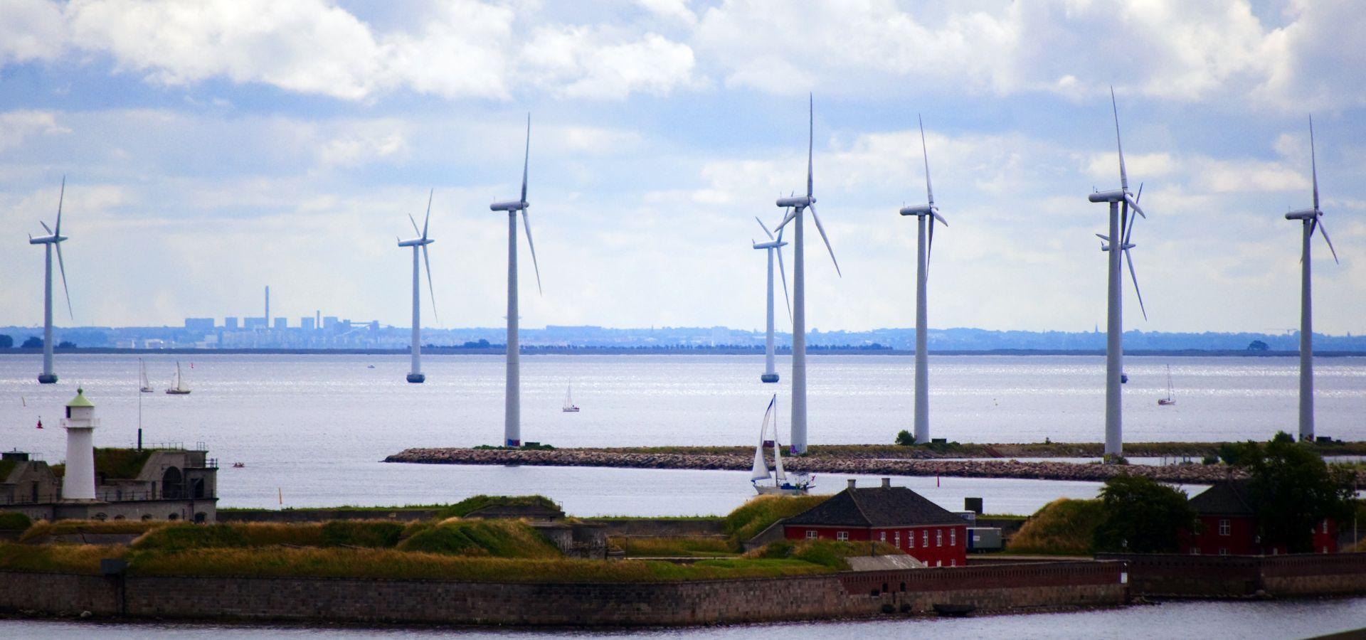 Von der Küste aus sind Windräder im Meer zu sehen, im Vordergrund ein kleines Haus