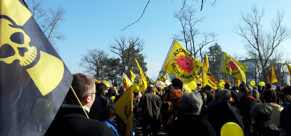 """Protest against the plant Fessenheim, with yellow """"Atomkraft? neine Danke"""" banners and a small crowd"""