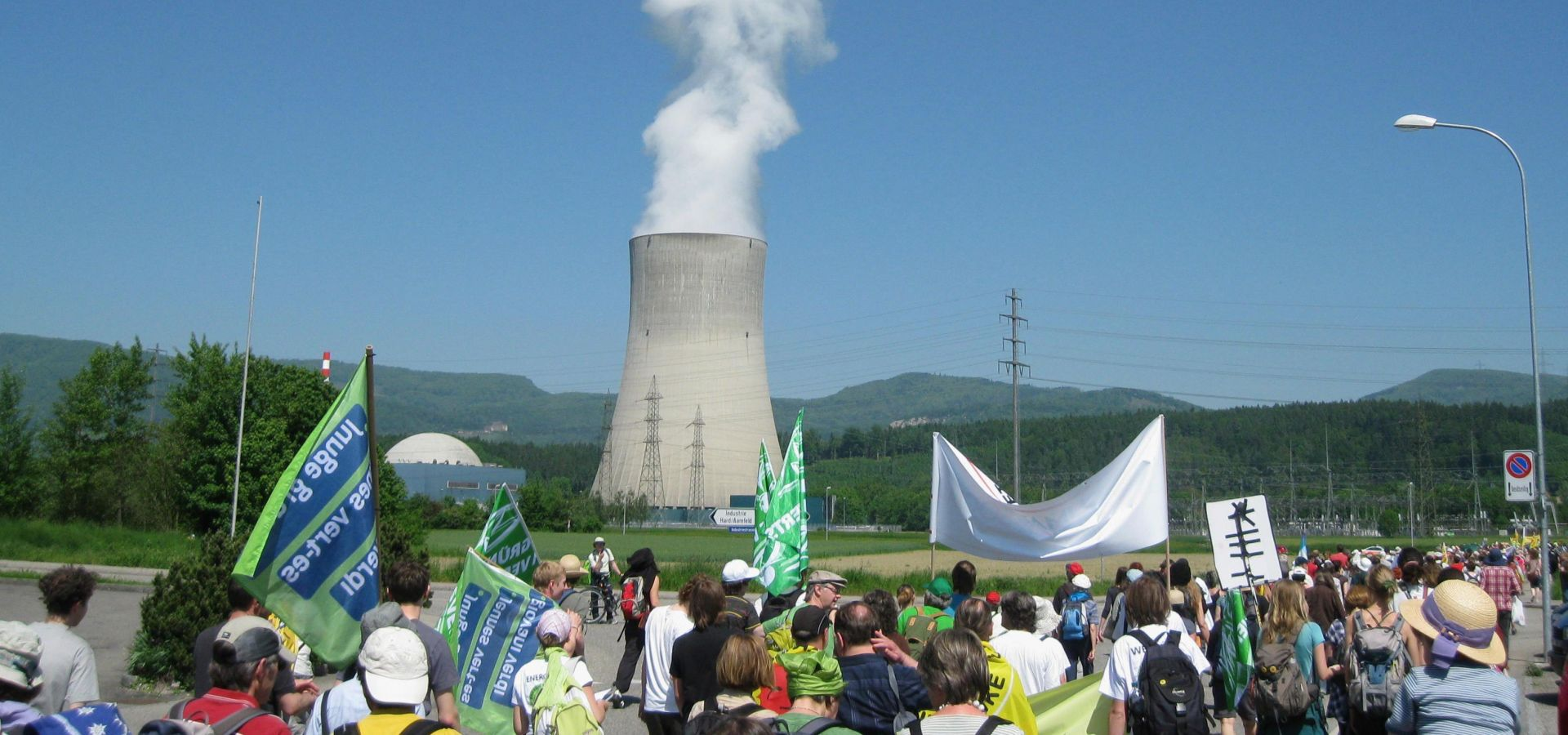 group of protesters by a nuclear plant on a sunny day
