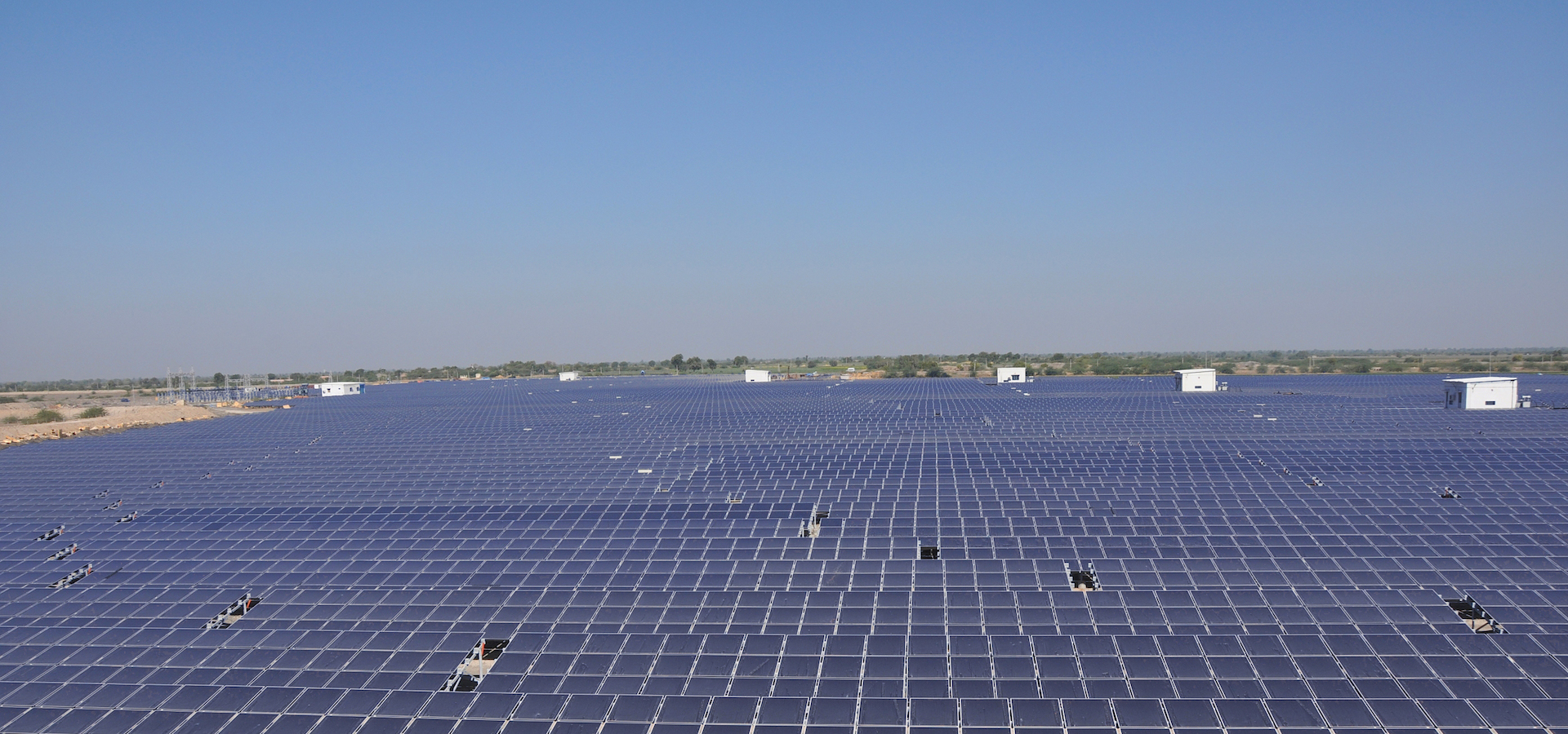 large field of solar panels with blue sky behind