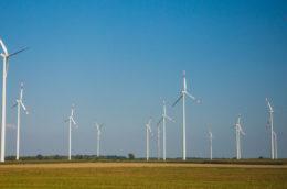 windmills in a flat field with blue sky