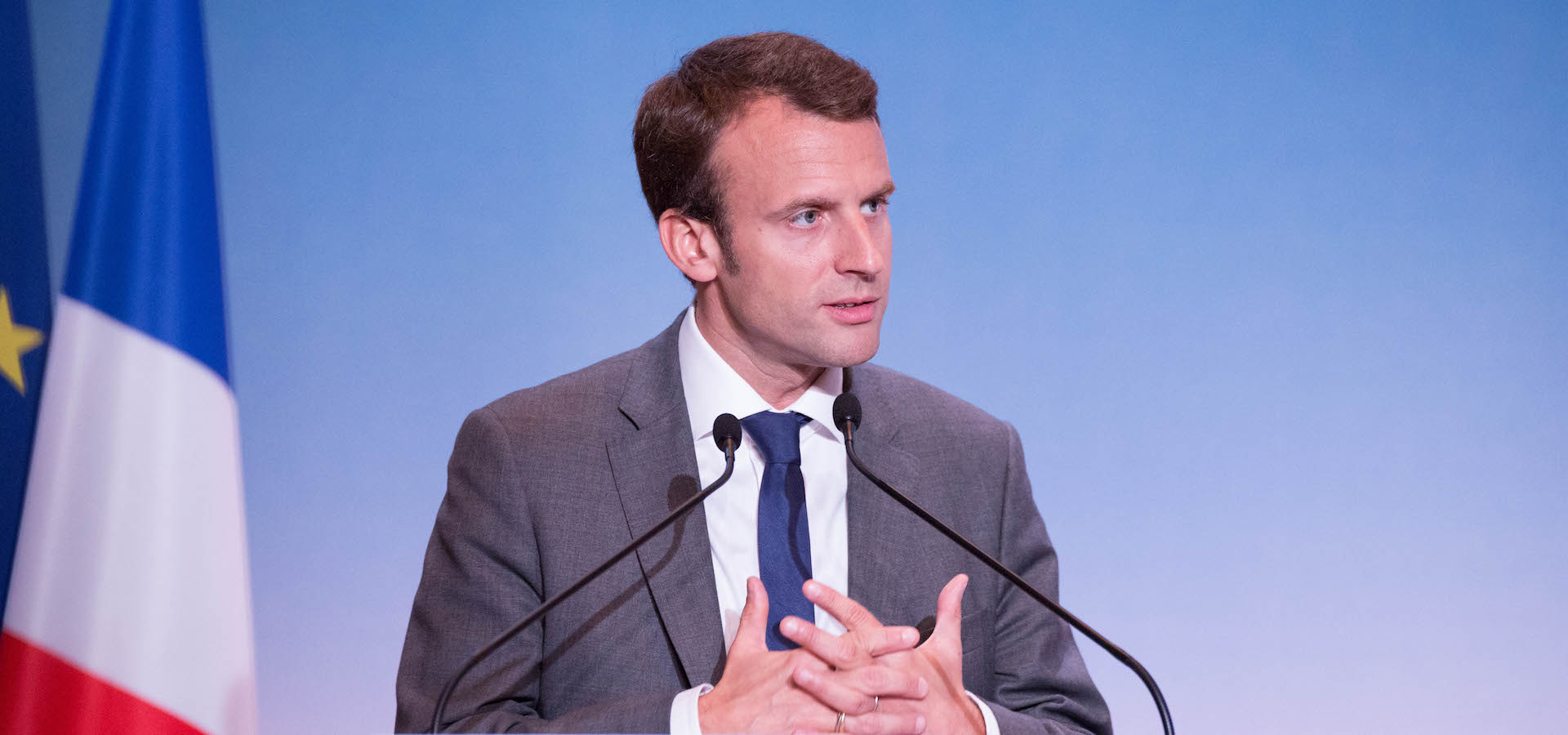 Emmanuel Macron (French President) speaking next to a French flag with blue backdrop