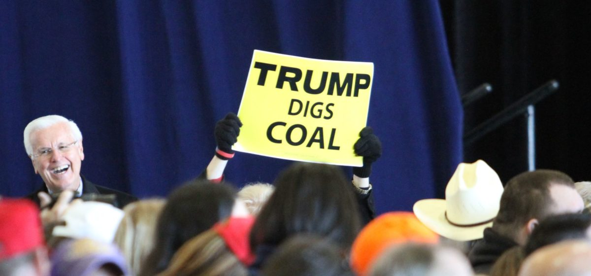 """a Trump supporter holding up a """"trump digs coal"""" sign at a rally"""