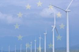 overlay of the EU flag on windmills along a coastline