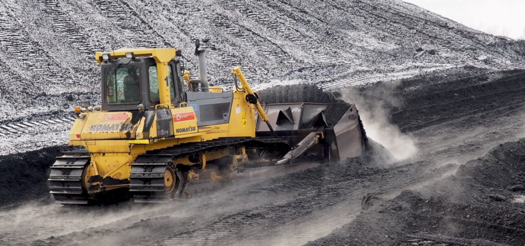 Komatsu D85 (yellow bulldozer) pushing a large pile of Indonesian coal in Power plant Ljubljana