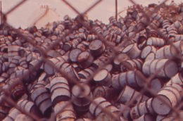 a mountain of damaged oil drums seen through a chain link fence