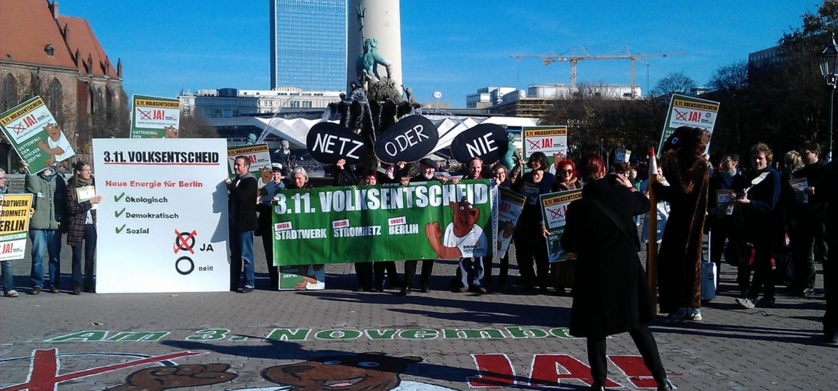 Gathering in front of the TV tower in Berlin, protesters with signs saying yes to new energy for Berlin