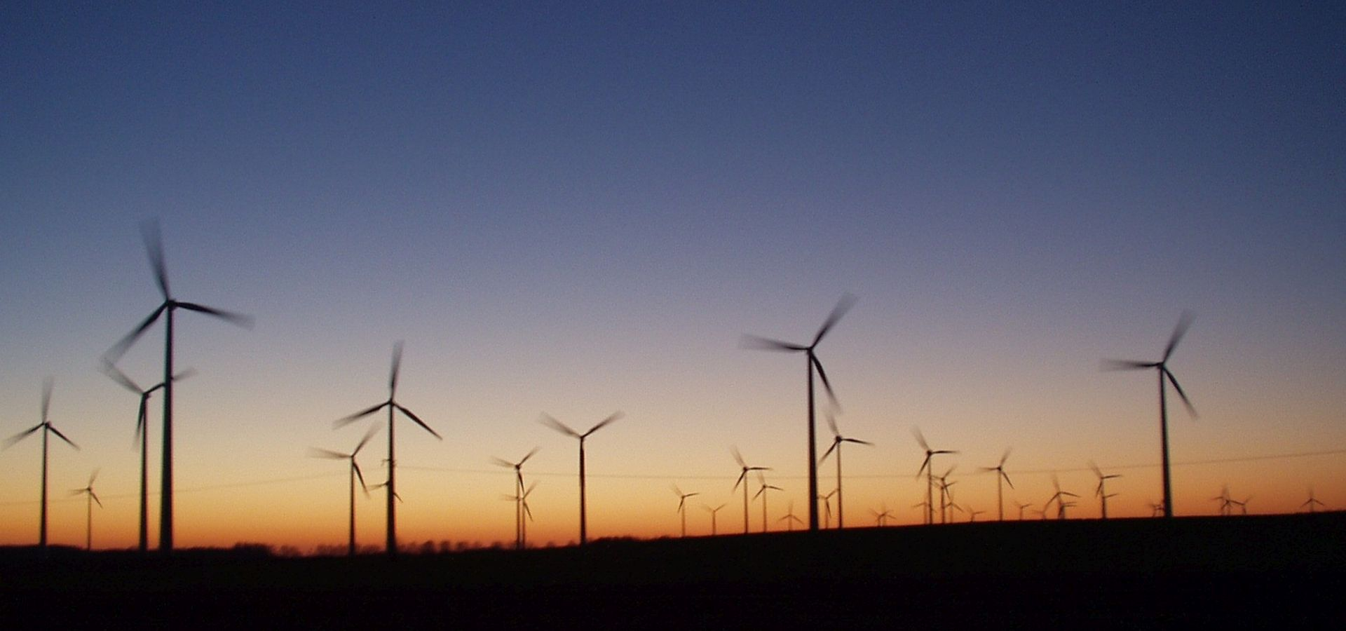silhouttes of wind turbines against a sunset