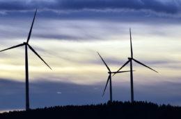 three windmills against a dark sky