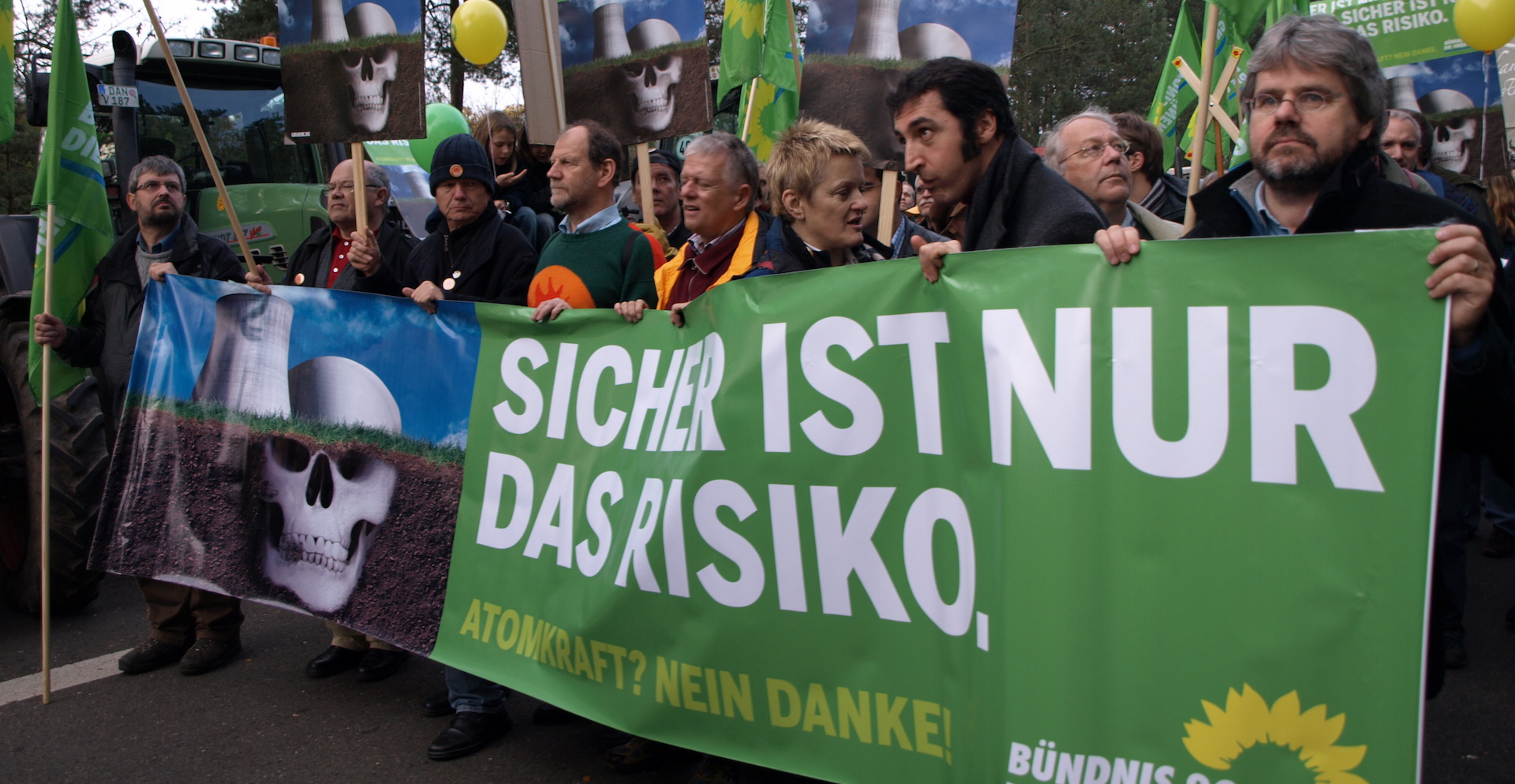 "German Green protesters holding signs that say ""Only risk is certain"""