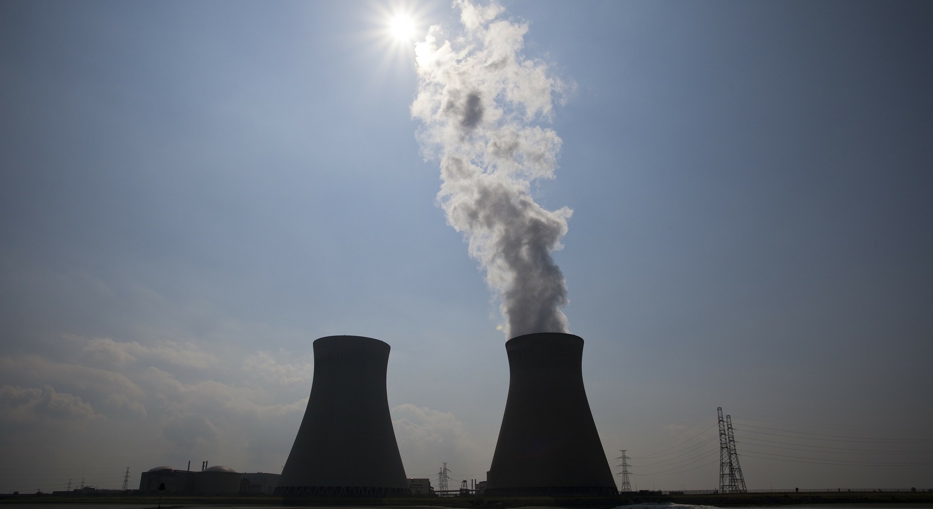 nuclear plant with steam rising from a tower, and the sun shining