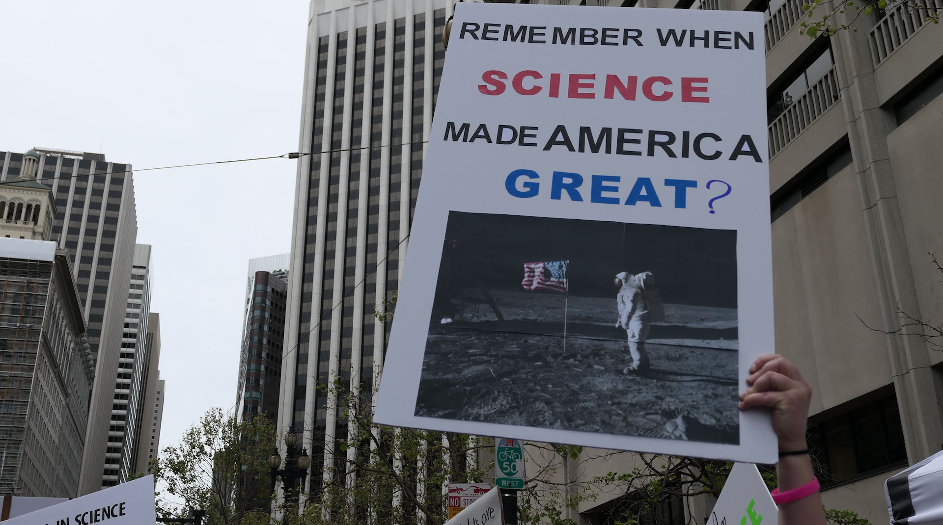 "Hand holding a sign that says ""Remember when science made america great?"" with a picture of the man on the moon"