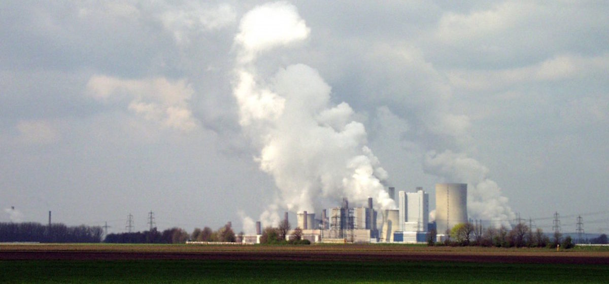 A large coal plant seen from far away, with clouds of steam rising from it