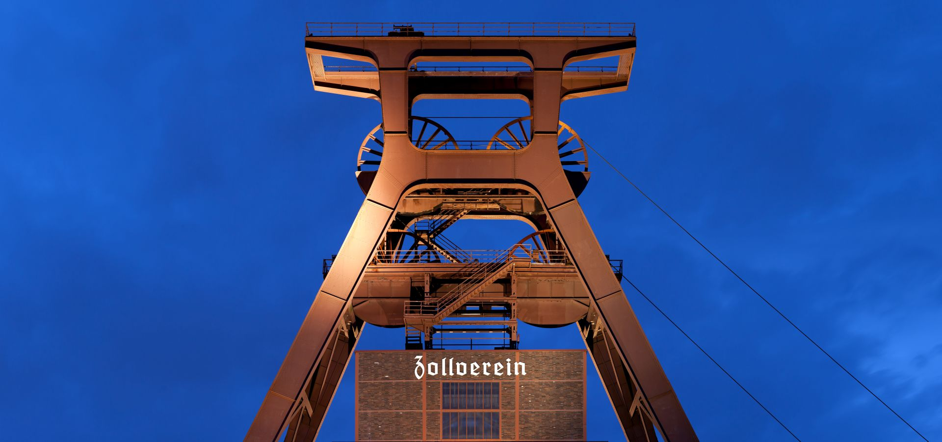 a picture of the former coal mine and museum Zollverein against a dark blue evening sky