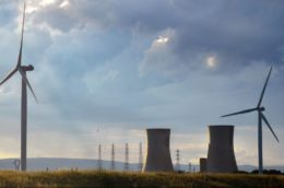 wind turbines in foreground with nuclear plant in the background with a clouded sunset