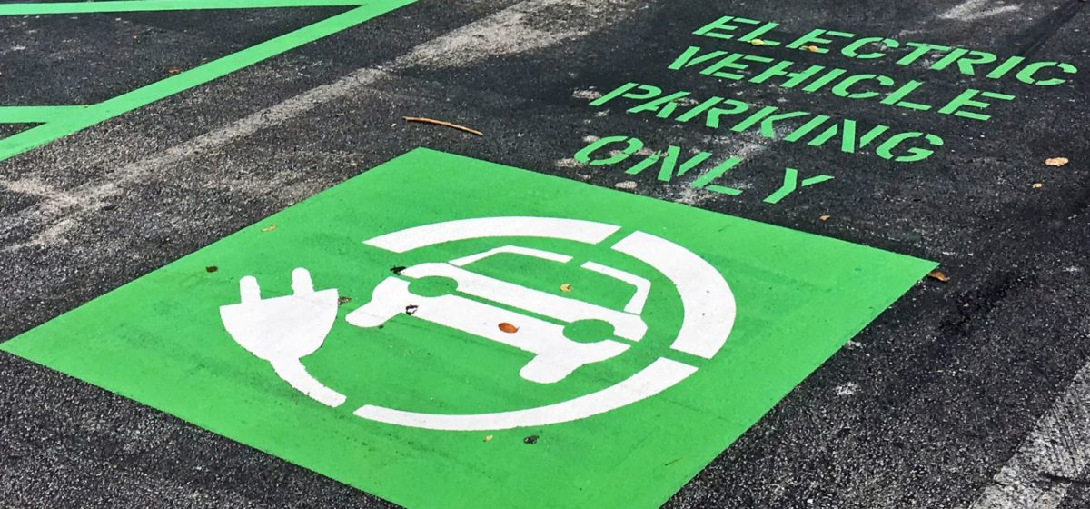 """sign reading """"electric vehicle parking only"""" in bright green at a charging station at a Mall in Miami, USA."""