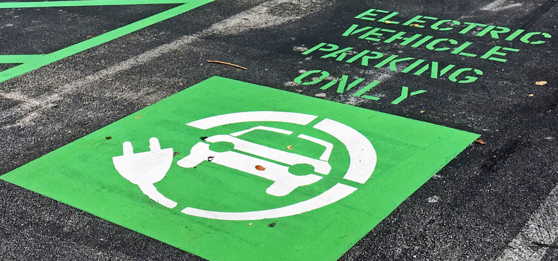 "sign reading ""electric vehicle parking only"" in bright green at a charging station at a Mall in Miami, USA."