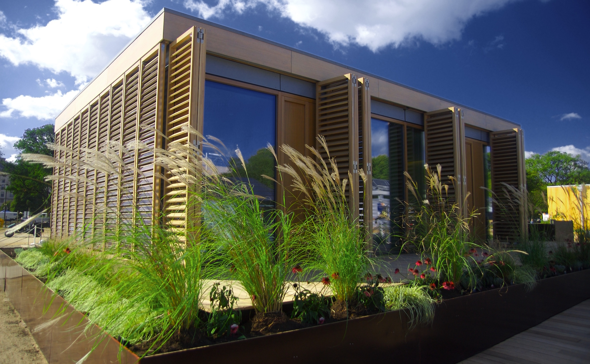 a small passive house building on Darmstadt University campus with a blue sky overhead and grasses growing in front of it