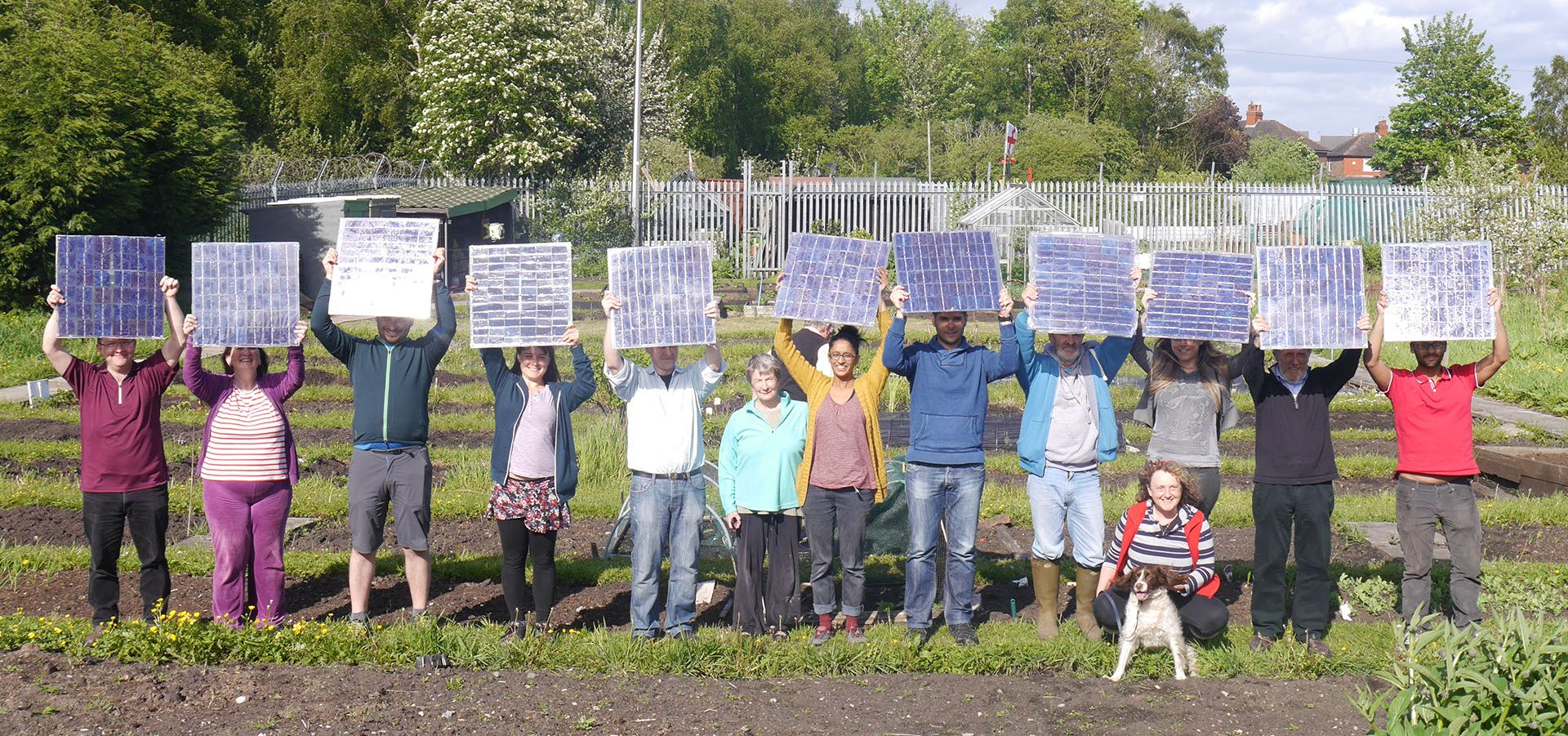 group of people of different ages, standing in a garden holding solar panels