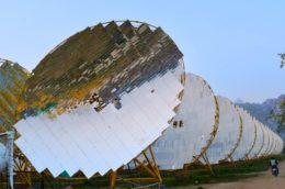 large circular solar panels from the India One solar plant, with mountains on the horizon