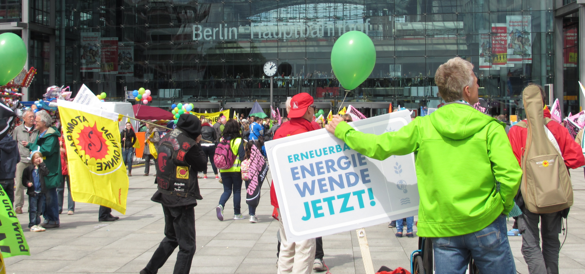 "Demonstration in front of the Berlin central train station, protesters with balloons and signs saying ""Nuclear? No thank you"" and ""Energy transition now!"""