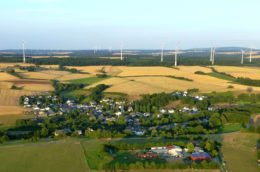 the village of Neuerkirch seen from above, surrounded by fields and wind turbines