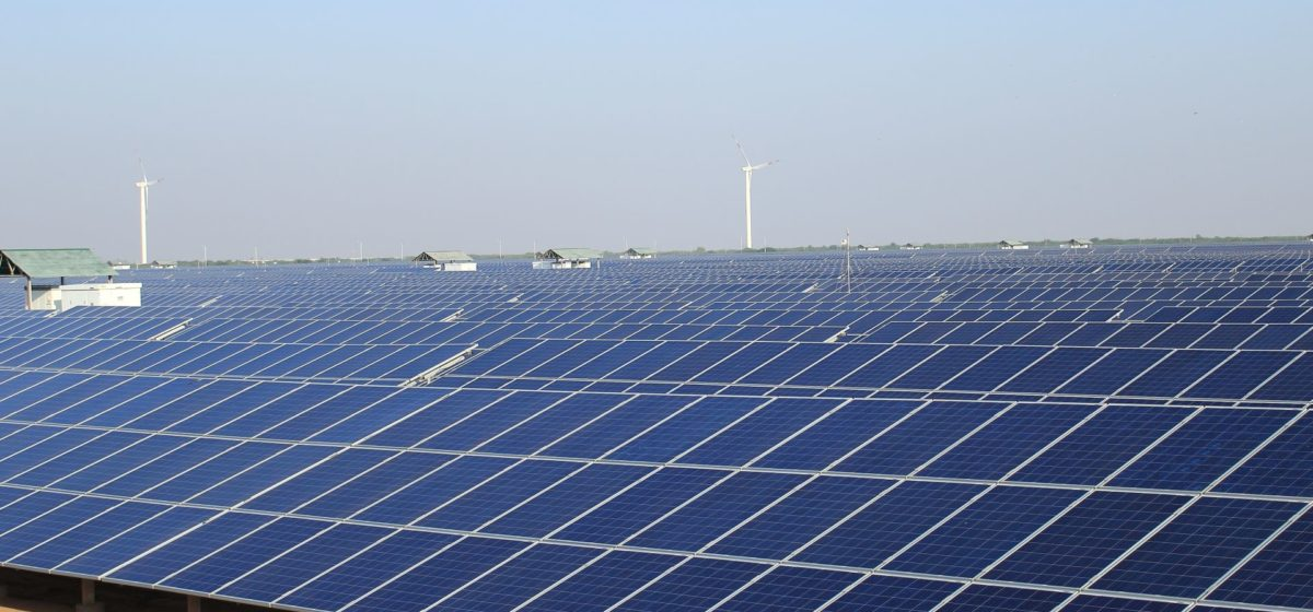 view of a field of solar panels with windmills interspersed