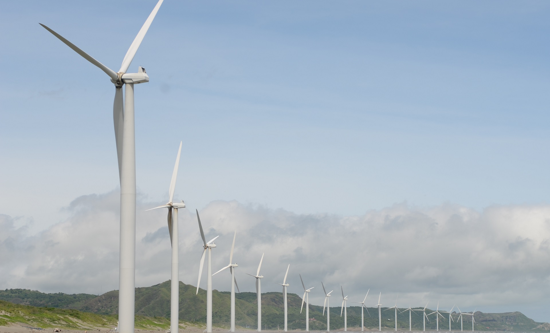a row of wind turbines with a mountain in the background