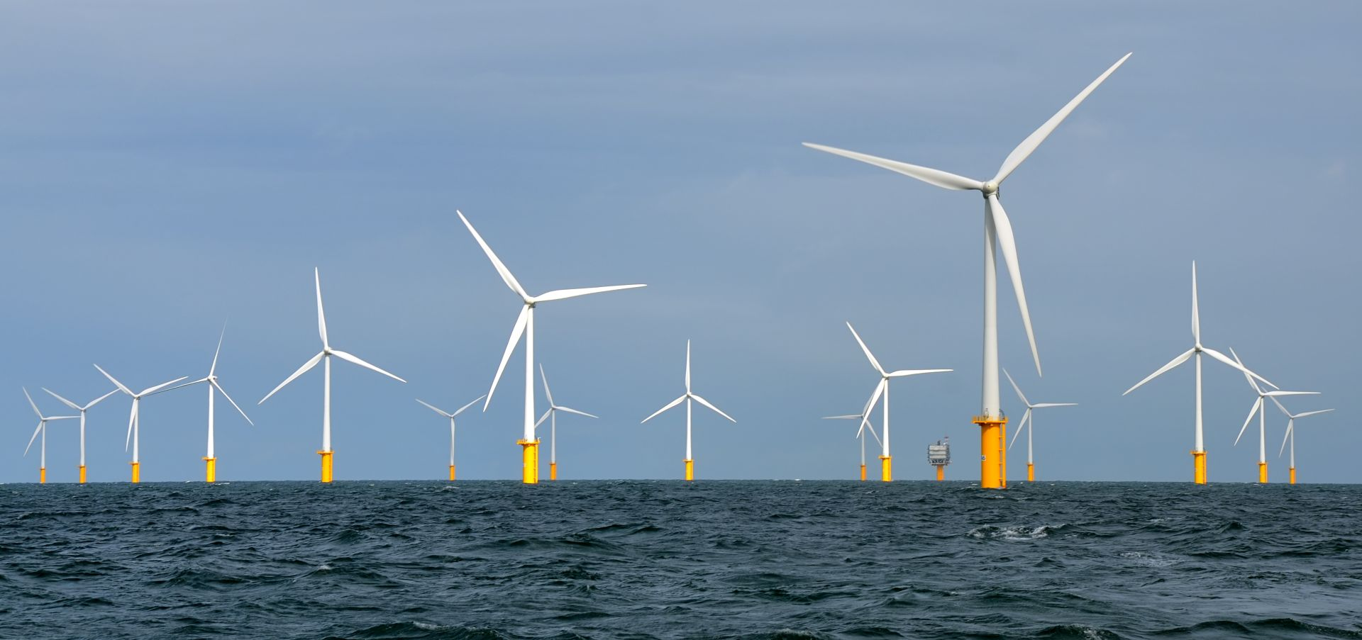 The Belwind turbines with a yellow base in the waves and a blue sky above