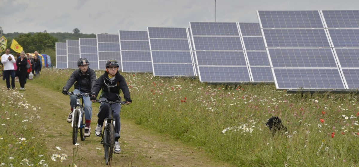 Visitors to the Westmill Solar Cooperative in the UK riding bikes in a field in front of solar panels