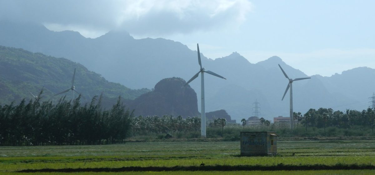 Windmills in a green field with low clouds and mountains in the background
