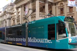 """Photo of a tram in Melbourne by a historic building, with an advertisement reading """"It's time to move to Melbourne"""" on the side"""