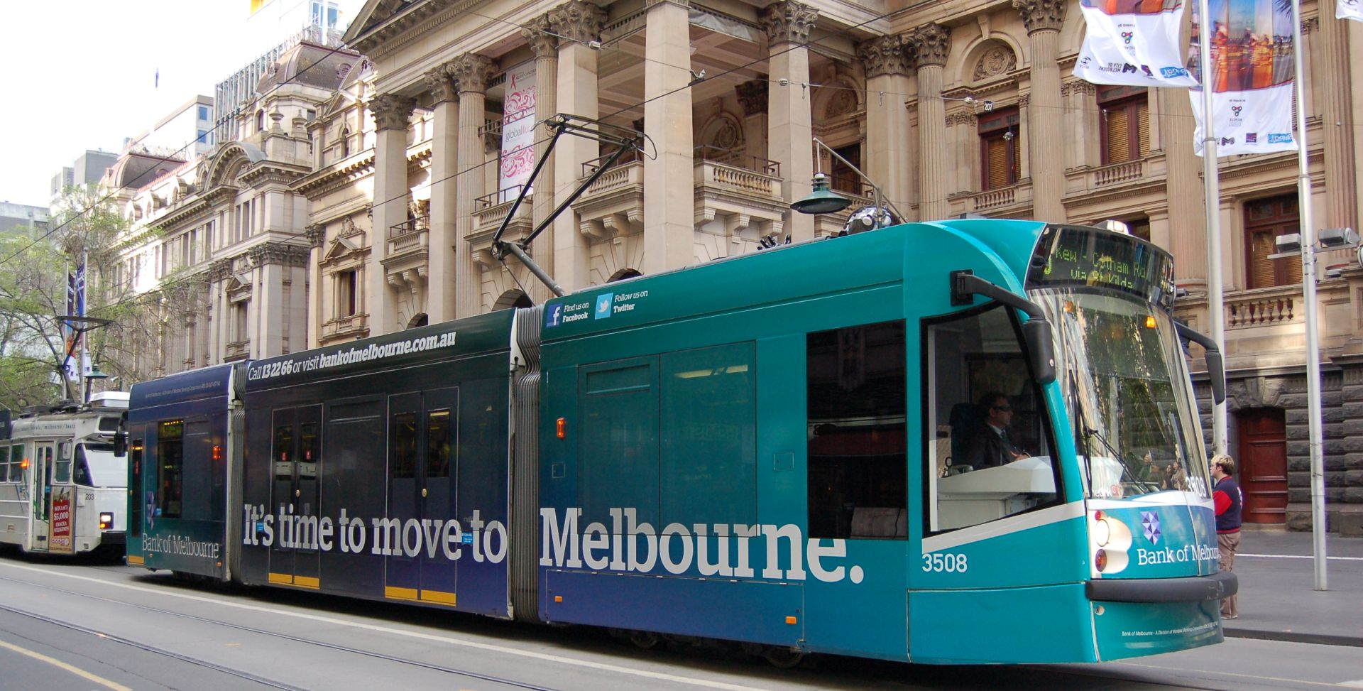 "Photo of a tram in Melbourne front of the city hall. On the tram is an advertisement reading ""It's time to move to Melbourne"" on the side"