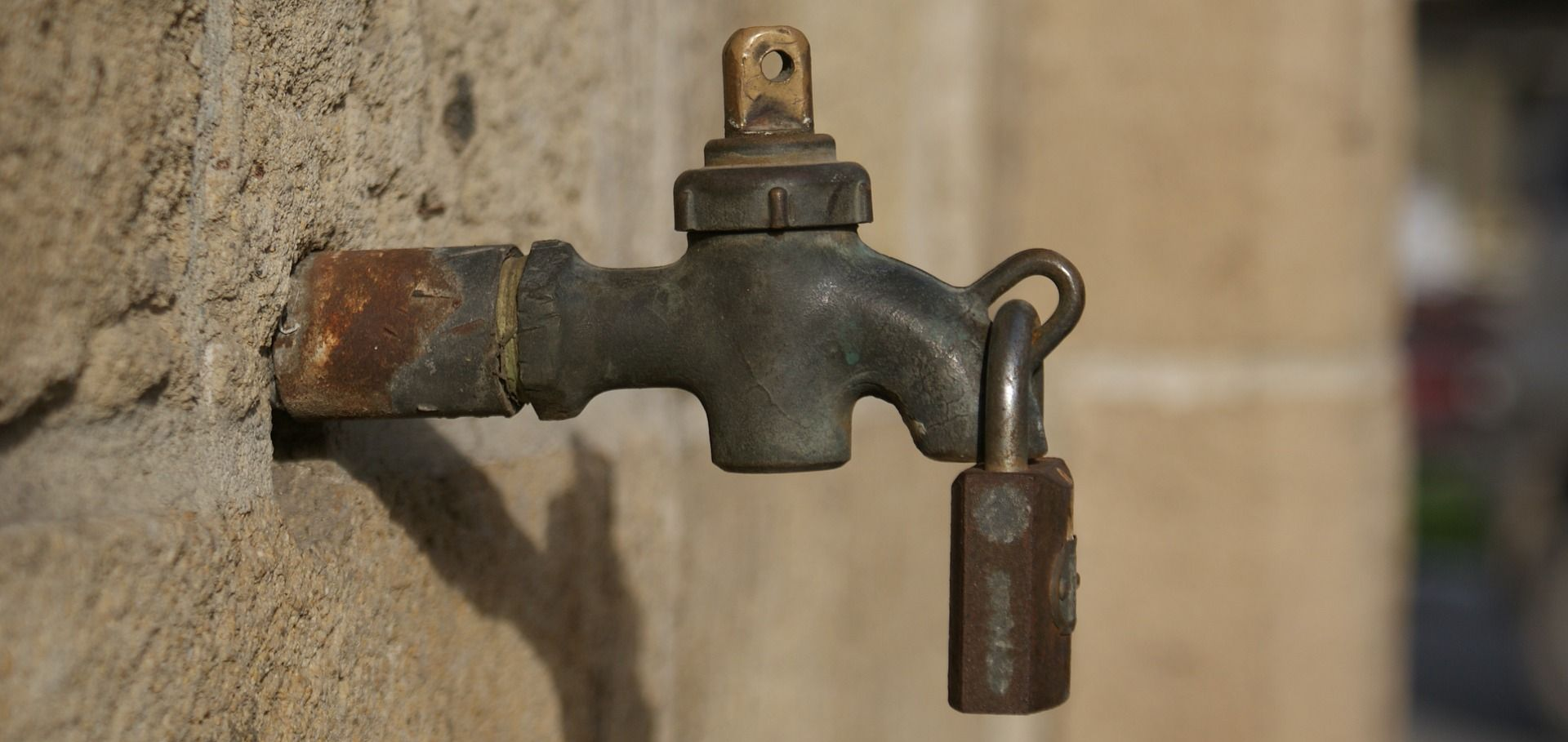picture of a water tap with a rusty lock on it
