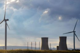 Wind turbines with nuclear cooling towers in the background