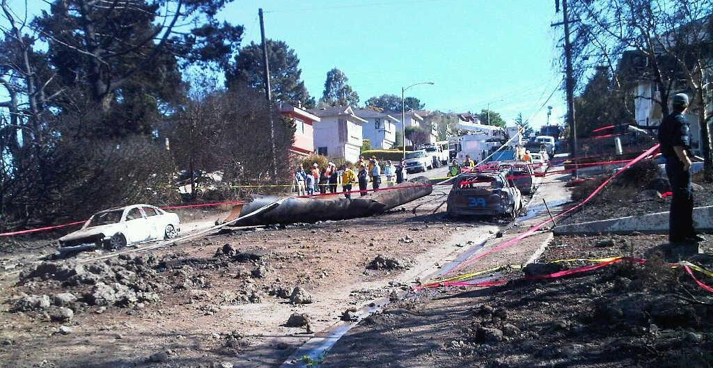 the aftermath of the San Bruno pipeline explosion, with ripped up street and burned cars