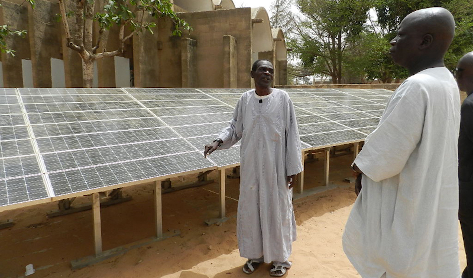 Two men in white robes standing next to a row of solar panels in Dakar, Senegal