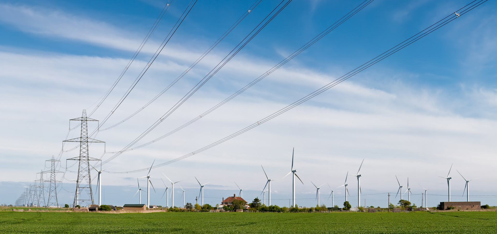Power lines and pylons looking towards the horizon with windmills in a green field