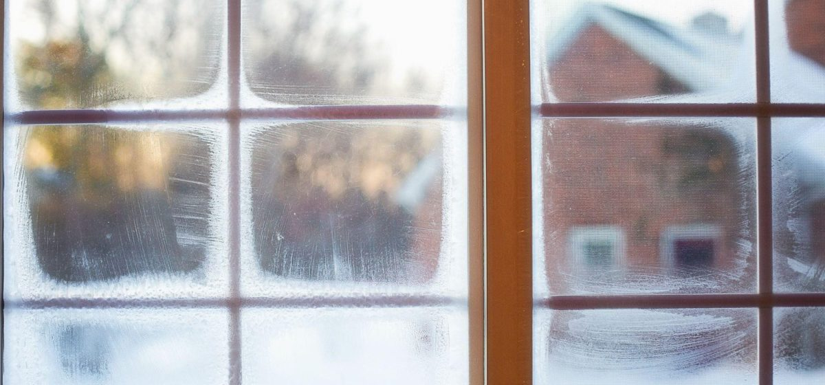 condensation on a window, with a snowy house seen outside