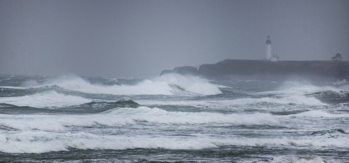 huge waves and gray sky with a lighthouse visible in the background at Yaquina