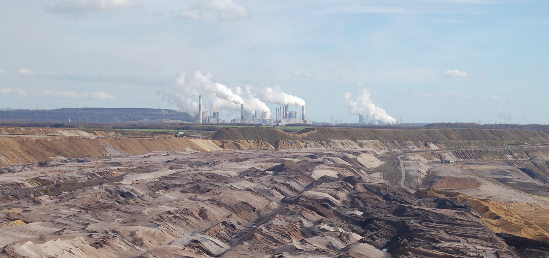 view of lignite lining fields with coal plant in the background